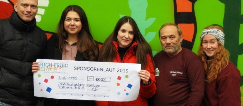 Zwei Schülerinnen der Erich-Fried-Gesamtschule überreichen einen Check über 1000,-€ an Herrn Stoll und Frau Grichel vom Abenteuerspielplatz Hasenkamp.